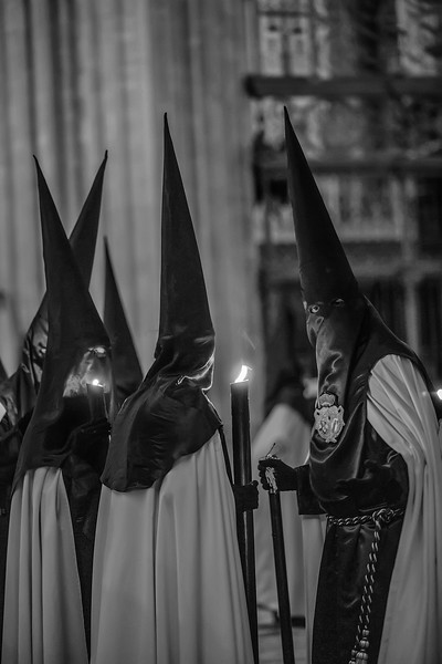 Baroque lights. Penitentes with candle lights in a procesion in the interior of the Cathedral of Sevilla, Spain, celebrating the Holy Week.