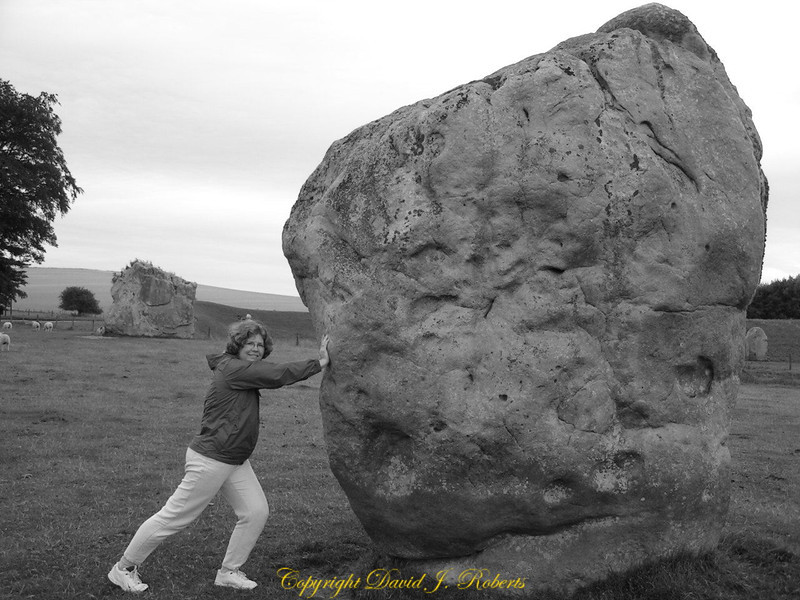 Allison shows that it is quite job to move one of the Avebury stones. Wiltshire, England.