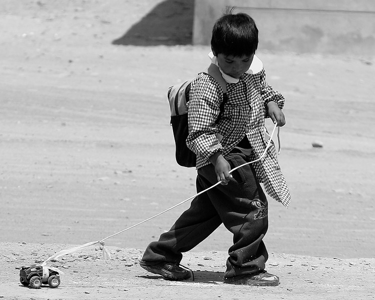 Child pulling toy truck through the street  Bella Union, Peru