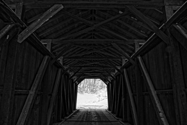 Wooden Tunnel<br /> <br /> This is the inside structure of a covered bridge .  The white you see on the wooden beams is snow that the wind blew in.  <br /> <br /> I have this same image except I added a glowing light at the end of the tunnel where you see trees and snow in this one.  It can be found at this link:     <br /> <br /> I think this image draws more attention to the structure itself.