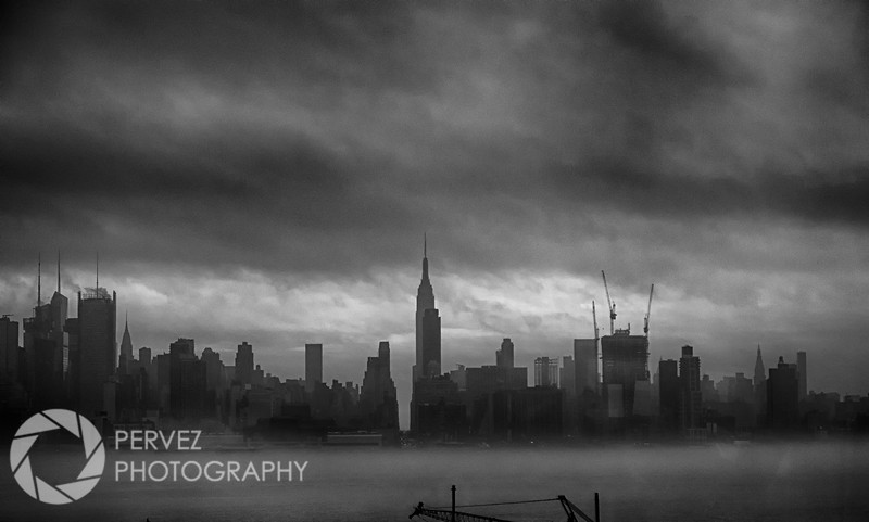 Shot of the New York City skyline in the fog after a rainy day. I happened to be on a bus stuck in traffic getting ready to enter the Lincoln Tunnel when I turned to my right and saw this spectacular visual. I scrambled for my camera gear and prayed that we'd be stuck long enough to let me get a few good shots as trucks and buses and cars drove by on the other side, making this a challenging photo to get. I did manage to get a few clear shots...if I hadn't, I'd be kicking myself for the rest of my life!