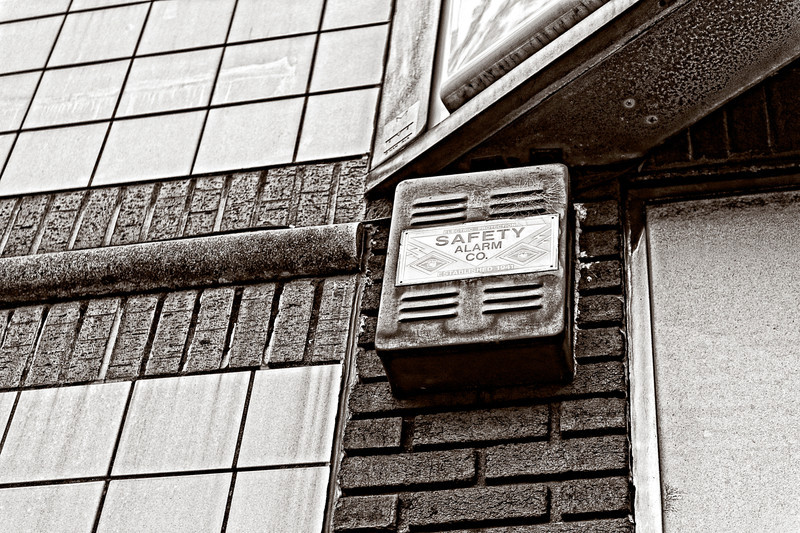 an alarm box located along a wall of a building on a corner in Five Points on Southside, Birmingham, Alabama
