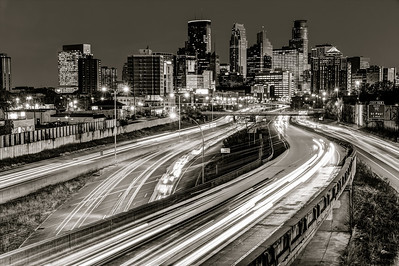 Colorless Commuting - City lights in the background and headlights in the foreground bring sharp contrast to this rush hour image of the Minneapolis skyline.