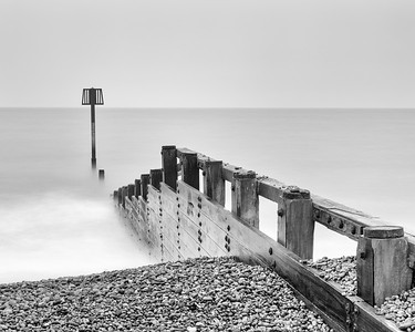 A groyne on the beach in Aldeburgh disappearing into the sea