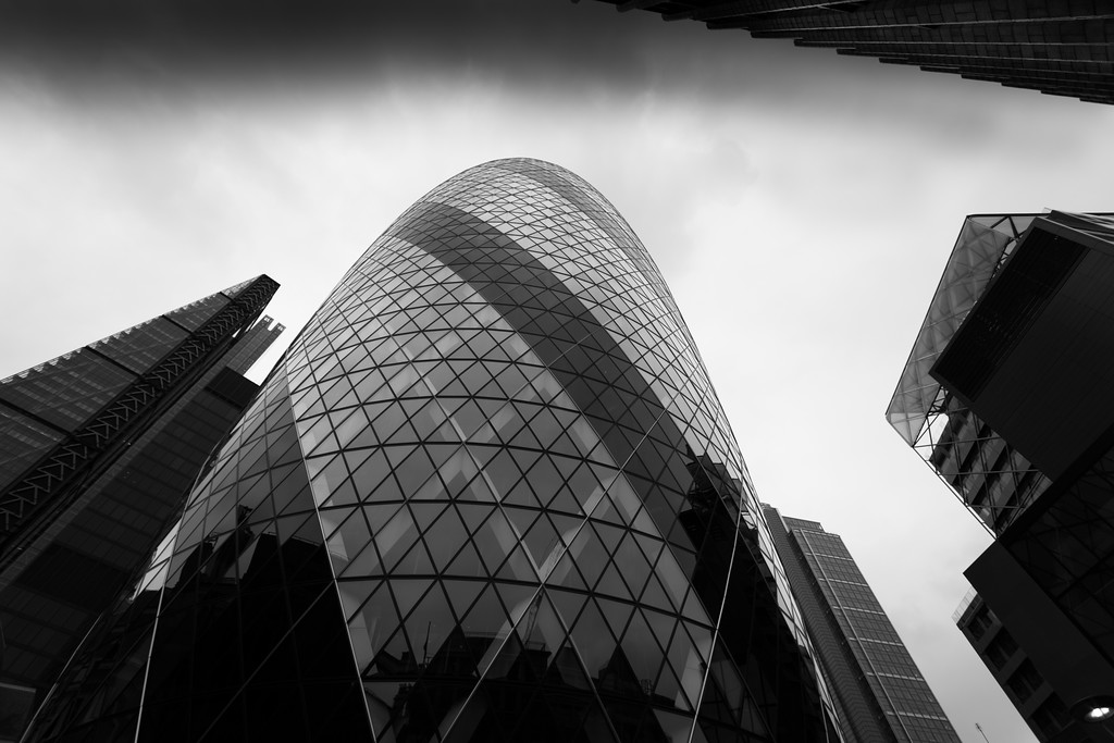 A black and white photograph of The Gherkin30 St Mary Axe (widely known informally as The Gherkin and previously as the Swiss Re Building) is a commercial skyscraper in London's primary financial district, the City of London. It was completed in December 2003 and opened in April 2004.With 41 storeys, it is 180 metres (591 ft) tall and stands on the former site of the Baltic Exchange, which was extensively damaged in 1992 by the explosion of a bomb placed by the Provisional IRA in St Mary Axe, the street from which the tower takes its name.
