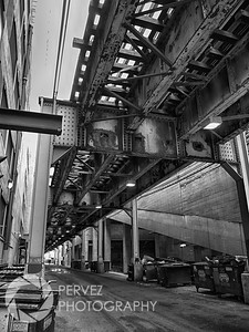 A train passes over an alley on the L