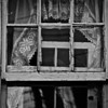 ghost in the window <p></p> Photograph of a window in an old house that is home to an antique and collectibles business.  You would not believe the appearance of the house.  The people inside are very friendly but I have no idea how they pass any sort of fire or safety inspection.  It is a favorite place for me to take photographs.  They have a certain amount of their inventory that sits outside the building all the time.  Equipment used and camera settings: <ul>    <li> Nikon D700 Camera</li>    <li> Nikkor 70.0-300.0 mm f/4.5-5.6</li>    <li> Focal length - 155mm</li>    <li> Tripod</li>    <li> Cable release</li>   <li> Metering Mode - Matrix</li>    <li> ISO 800</li>    <li> EV (exposure value) -1</li>    <li> Aperture f/8.0</li>    <li> Shutter Speed 1/125th second</li>    <li> White Balance - Auto</li>    <li> Bit Depth 16</li>   </ul>