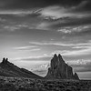 Black and white photo of the  sun setting behind the Shiprock volcanic rock formation near Shiprock, New Mexico