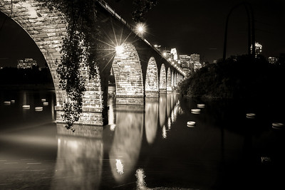 Floating Under the Golden Arches - In Black and White.   A local artist placed several white innertubes in the Mississippi River in downtown Minneapolis.  In this image they appear to be organizing themselves to float under the Stone Arch Bridge but can't quite muster the courage to go into the light.  The night skyline of Minneapolis looms in the background.