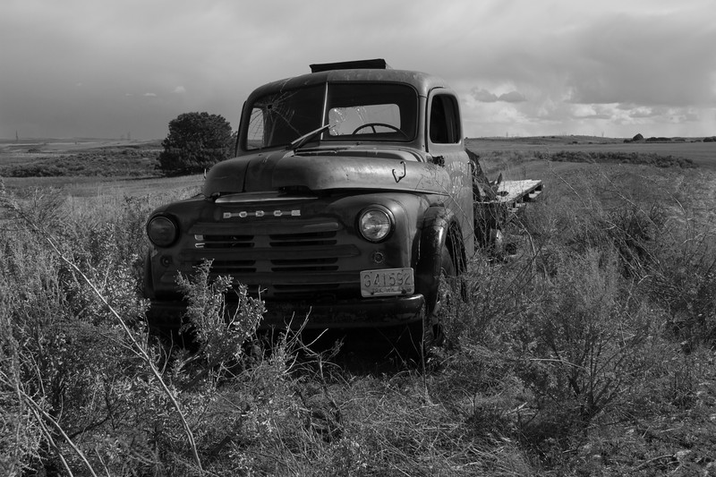 Bullet ridden Dodge flat bed Black and white.