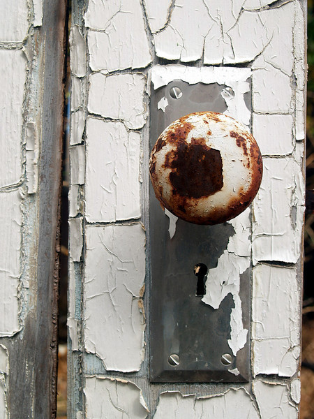 Doorknob and peeling paint on an abandoned farmstead near Soledad in the Gavilan Mountain Range, California.  2007