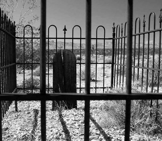 Iron bars do not protect against everything.  Bullfrog Mine Cemetery near Rhyolite (ghost town) Nevada.  2007.