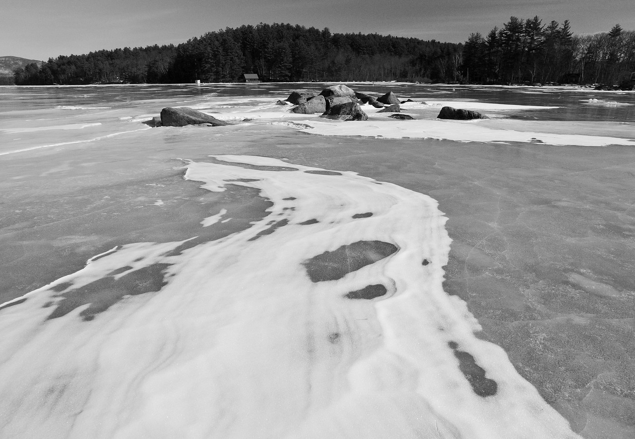 Snow blows and eddies across the nearly mirror surface of Squam Lake.