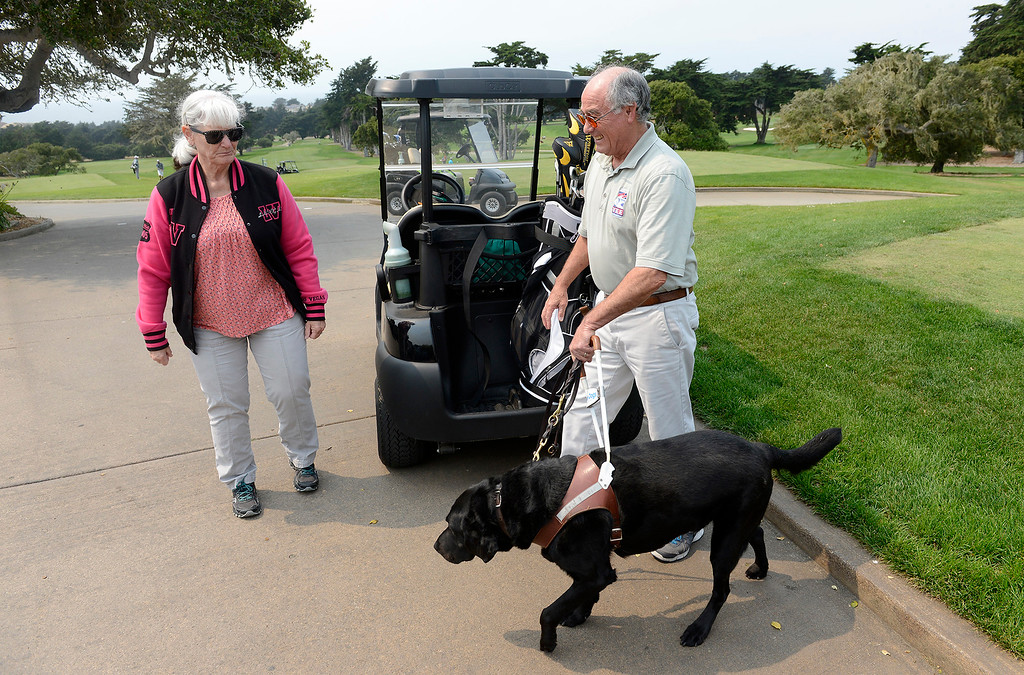. Barbara Franco helps her husband U.S. Navy veteran, Carlos Franco with his service dog Miguel on the practice range at Bayonet and Black Horse Golf Club in Seaside on Tuesday, August 7, 2018.  Franco who is blind is learning golf through the PGA HOPE (Helping Our Patriots Everywhere) program at the Seaside golf course.  (Vern Fisher - Monterey Herald)