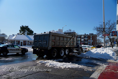 a steady stream of dump trucks come in, are loaded with snow, then they haul it away