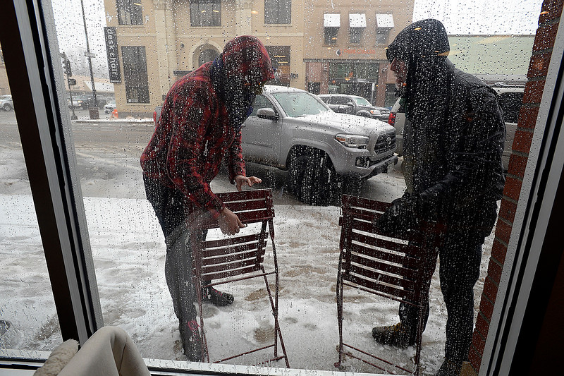 Coffee Tree employee Sarah Menzies, left, and customer Shaun Vavra pick up chairs outside the coffee shop in downtown Loveland Wednesday, March 13, 2019, as they prepare to close early becuase of blizzard conditions.  (Photo by Jenny Sparks/Loveland Reporter-Herald)