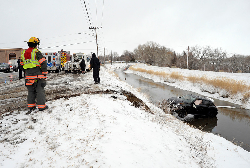 . A Loveland Fire Rescue Authority firefighter stands by as tow truck drivers prepare to pull a car out of the Big Barnes Ditch while other firefighters secure an oil absorbant boom downstream Wednesday, March 13, 2019, after the driver ended up in the ditch on Eighth Street near Van Buren Avenue during a storm in Loveland. The driver was not injured in the one-car accident.  (Photo by Jenny Sparks/Loveland Reporter-Herald)
