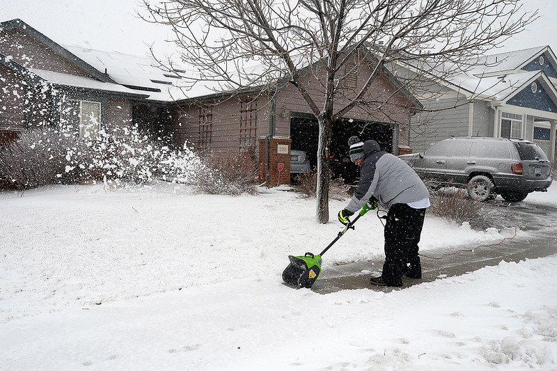 Brent Oglesby uses a power shovel to clear his sidewalk Wednesday, March 13, 2019, on the 1200 block of east 50th Street in north Loveland. (Photo by Jenny Sparks/Loveland Reporter-Herald)