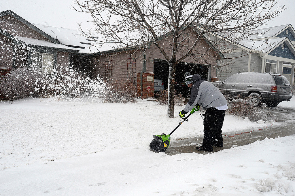 . Brent Oglesby uses a power shovel to clear his sidewalk Wednesday, March 13, 2019, on the 1200 block of east 50th Street in north Loveland. (Photo by Jenny Sparks/Loveland Reporter-Herald)
