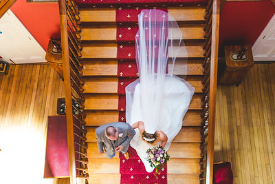 Bride with her father walking down the stairs.