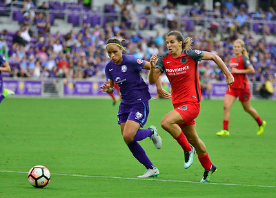 Rain falls as Tobin Heath of the Portland Thorns races for the ball against Monica Hickman Alves of Orlando Pride at Orlando City Stadium in Orlando, Fl.