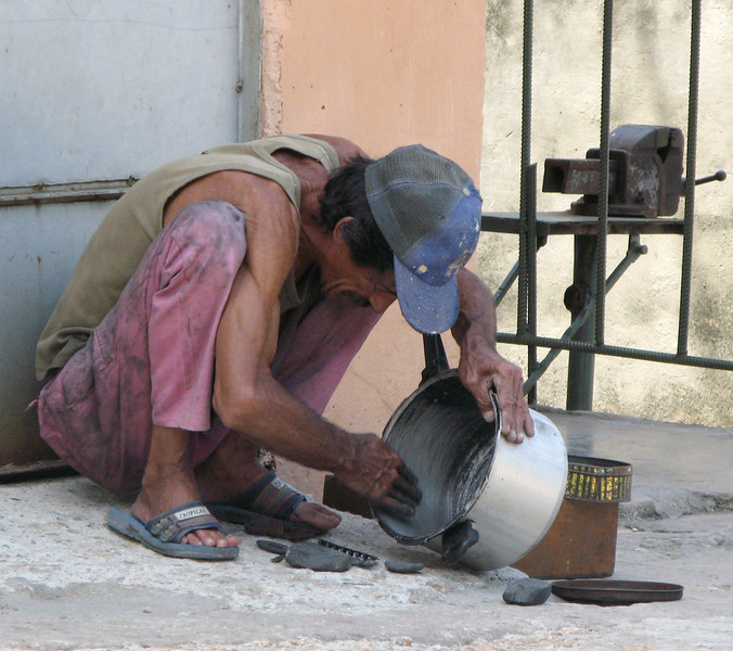 Casa owner. This is the owner of the house. He sits across the street repairing pots and pans because he is afraid the house will fall down on him if he sits in front of his own house.