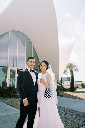 retro Neon Museum micro wedding in Las Vegas - modern bridal jumpsuit with skirt and pockets - vintage hairstyle with waves - black and white polka-dot-purse - Kristen Kay Photography - Photo and Super 8 Video