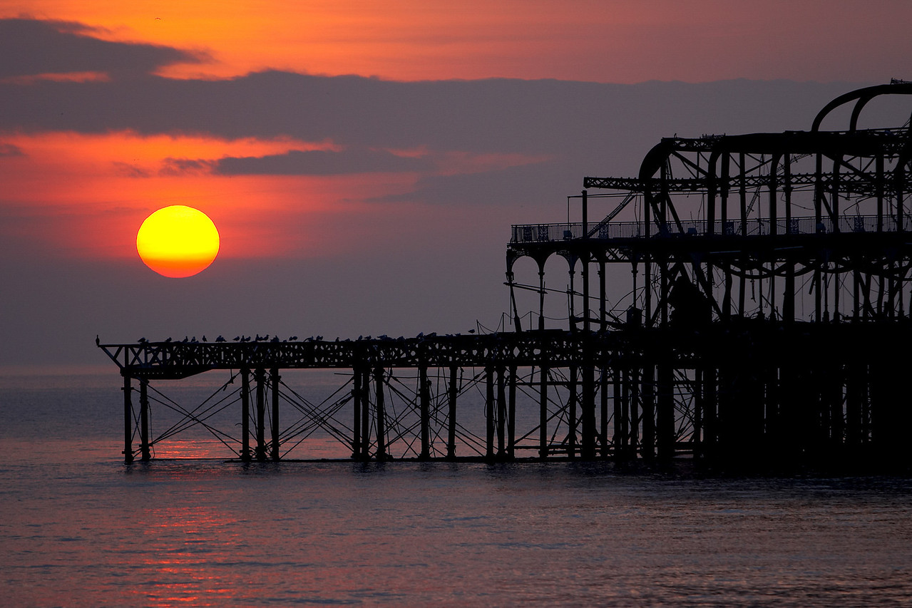 The setting sun behind Brighton`s West Pier