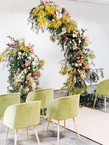 The Doyle - modern, industrial Las Vegas Wedding Venue - Kristen Krehbiel - Kristen Kay Photography - bright pink peony, orchid, organic floral archway with yellows and greenery - olive green ceremony chairs - Type A Society