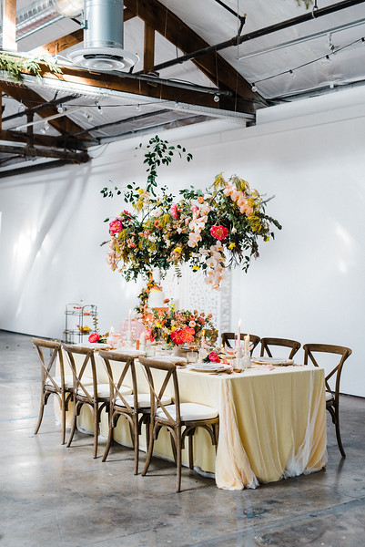 hanging floral installation with pink peony and orchids by Oak and Owl - The Doyle - Las Vegas Wedding Venue - Kristen Krehbiel - Kristen Kay Photography - tablescape with wooden chairs and yellow tablecloth - art direction by Type A Society