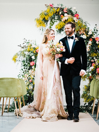 Ceremony - The Doyle - modern, industrial Las Vegas Wedding Venue - Kristen Krehbiel - Kristen Kay Photography - bright pink peony, orchid, organic floral archway with yellows and greenery - Carol Hannah Gown, Marjorie, with long veil - Type A Society, Carrie Moe