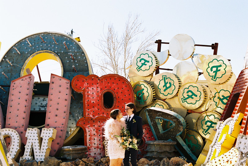 Neon Museum Las Vegas Wedding Ceremony - Unique Elopement Locations - Kristen Kay Photography - blue suit and short long sleeve lace dress - view more from this rad Elvis inspired intimate wedding in colorful, fun Downtown Vegas -- #neonmuseum #vintage #elopement #neon