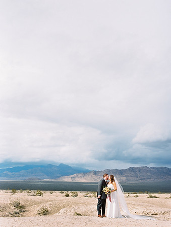 sweetheart neckline gown with long cathedral veil by Robert Bullock // bridal bouquet with protea, scabiosa, eucalyptus and garden roses - Rooted Willow // Las Vegas desert elopement // Las Vegas Elopement & Intimate Wedding Photographer - Kristen Krehbiel - Kristen Kay Photography // Portra 400 - film // dark blue clouds with illuminated foreground