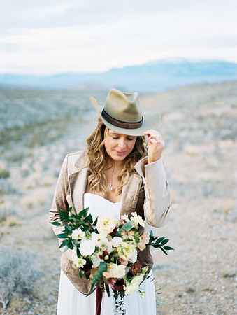 bride wearing grandfather's cowboy hat - desert elopement in Las Vegas - Mt. Charleston // white and red floral bouquet with protea by Rooted Willow // Las Vegas Elopement Photographer - Kristen Krehbiel - Kristen Kay Photography