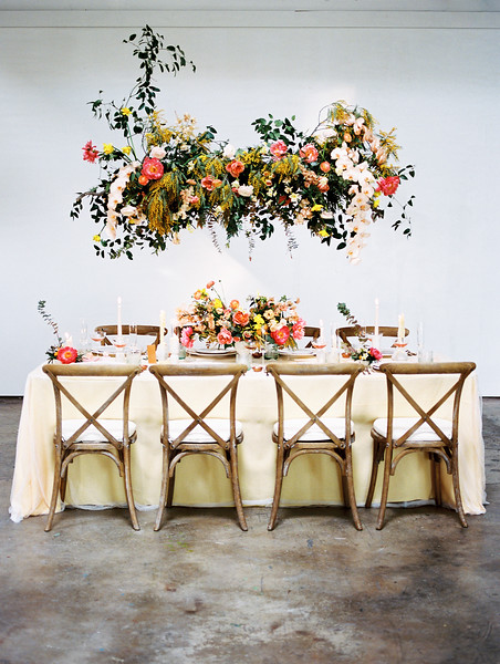 hanging floral installation with pink peony and orchids by Oak and Owl - The Doyle - Las Vegas Wedding Venue - Kristen Krehbiel - Kristen Kay Photography - tablescape with wooden chairs and yellow tablecloth