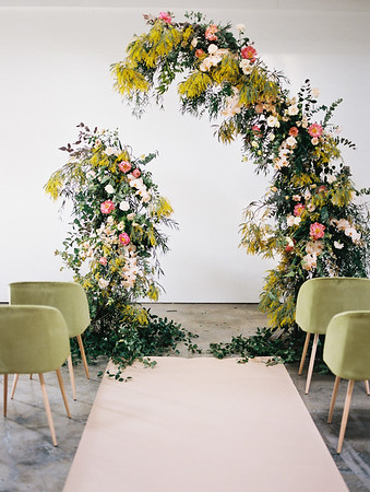 The Doyle - modern, industrial Las Vegas Wedding Venue - Kristen Krehbiel - Kristen Kay Photography - bright pink peony, orchid, organic floral archway with yellows and greenery - olive green ceremony chairs