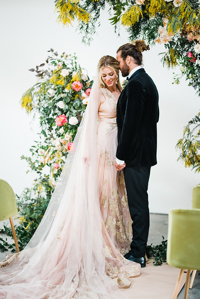 Ceremony - The Doyle - modern, industrial Las Vegas Wedding Venue - Kristen Krehbiel - Kristen Kay Photography - bright pink peony, orchid, organic floral archway with yellows and greenery - Carol Hannah Gown, Marjorie, with long veil