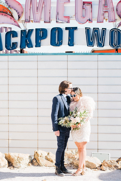 Neon Museum Las Vegas Wedding - Unique Wedding Locations - Kristen Kay Photography - long sleeve floral lace dress with fur, blue suit - view more from this rad, vintage Elvis inspired intimate wedding in colorful and fun Downtown Vegas -- #neonmuseum #vintage #elopement #neon #suit #feathers