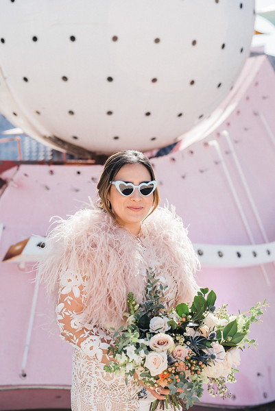 Neon Museum Las Vegas Wedding - Unique Wedding Locations - Kristen Kay Photography - long sleeve floral lace dress with fur - view more from this rad, vintage Elvis inspired intimate wedding in colorful and fun Downtown Vegas -- #neonmuseum #vintage #elopement #neon #lace #feathers