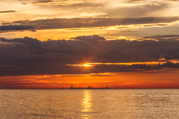 The sun above the Chicago skyline, viewed from near the Indiana Dunes State Park (Porter Beach) in mid-July.