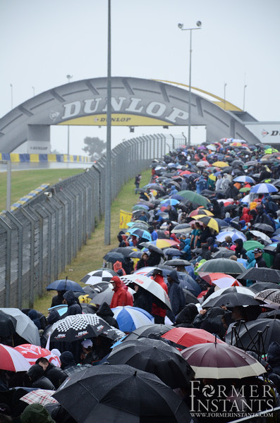 People Lining the Track in the Rain