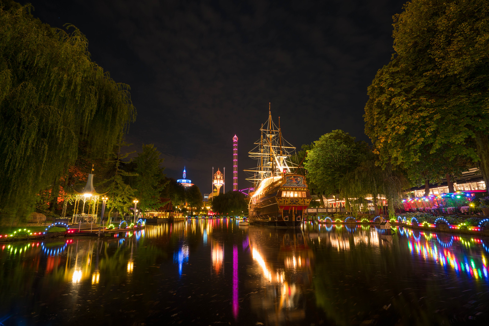 Marvel at the lights reflecting of the lake in the middle of Tivoli Gardens