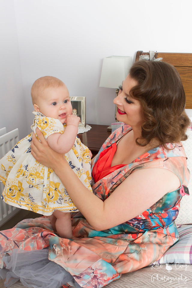 Vintage styled mother and her baby daughter in a flowery dress, Glasgow