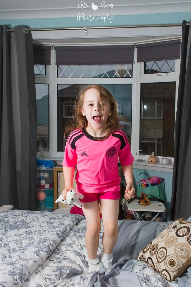Glaswegian little girl jumps on bed wearing pink Scotland strip