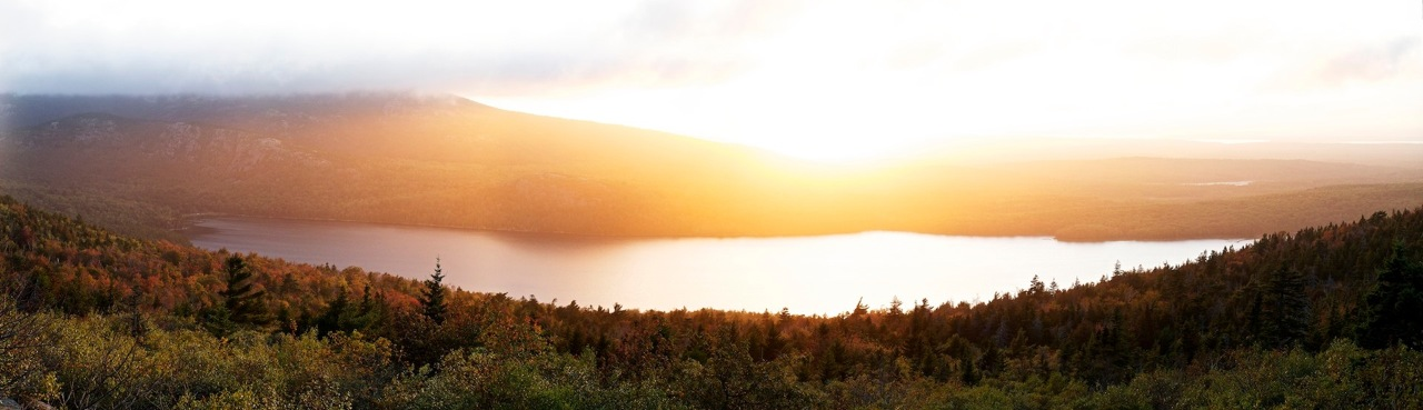 """Sunset on Cadillac Mountain - Acadia National Park: File# 1130643  <a href=""""http://www.tom-hill.biz/Galleries/Scenics/Elsewhere-Japan-Plains-Maine/20972581_TxHZrc#!i=1666661145&k=cPL4Rpp"""">  Link To Original Image </a>  Maine was my last state.  When I rode into Maine on the day this image was taken it was the 50th I'd ever stepped foot into.  I'd never been there let alone had any knowledge of where to shoot.    I followed friends advice and setup camp at a awesomely forested/rustic camp site just out of Acadia National Park, but I had no idea where to shoot the coming sunset.  All I did after picking a site was rush to the park and hope for the best.  With nothing else to guide me I followed what I normally do in such situations, seek the high ground.  There is no higher ground in this park than Cadillac Mountain.  I didn't even make it to the summit.  I was diverted by the view off an impossibly grounded turn-out up the mountain.  Good thing I stopped because the sunset was wonderful.  Not only that, the tiny little camera I had did a great job with rendering the moment.    Sometimes fortune happens to those that don't plan.  It sure did for me on this day."""