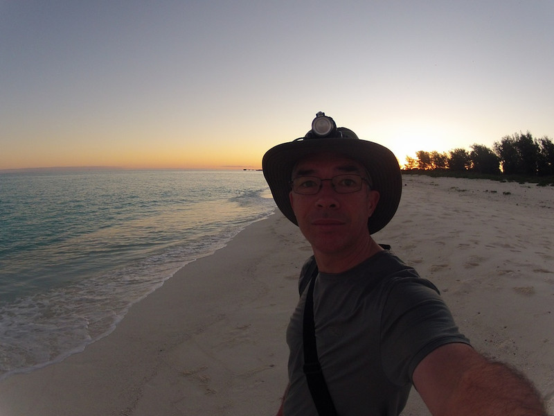 Midway Sunrise Self-Portrait - Midway Island, North Pacific, File #1152120<br /> <br /> Of course, not everything has to be about nature images shot with my amazing Nikon D3.  Sometimes I only have to use my tiny little GoPro POV (point of view) camera that fits in the palm of my hand.  Even for a tiny little thing like it is, it does a great job, subject not withstanding.  <br /> <br /> No, my forearms are not Popeye big.  It's a visual illusion related to the very wide-angled lens on this camera and how i'm holding the camera.<br /> <br /> The thing on top of my hat is a head-lamp.  Not that I needed it all that much on this morning because the moon was full, which you'll see more in a bit.