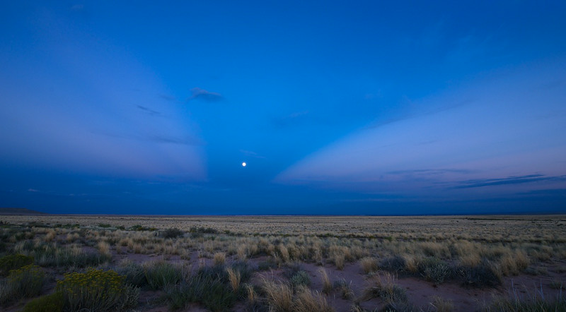 """Ooh-Child, Things Are Going To Get Better"" - 16 August 2014<br /> <br /> Moonrise Over Little Painted Desert - Winslow, Arizona<br /> <br /> Link to full sized image:  <a href=""http://www.tom-hill.biz/Galleries/Scenics/Arizona/i-hw86FkV/A"">http://www.tom-hill.biz/Galleries/Scenics/Arizona/i-hw86FkV/A</a><br /> __________<br /> <br /> The song popped into my head. <br /> <br /> ""ooh child, things are going to get beettter, ooh child, things will get briiiighter.""  <br /> <br /> The catchy song from the the early 80's was making me hum its lyrics as I sat there, sat there on the bed at the emergency room.  <br /> <br /> ""Ooh Child..."" I'm singing this to myself when I start smiling at the irony of me in an emergency room with my finger wrapped in an enormous bandage, IV sticking out of the other arm, heart rate monitor and blood pressure cuff leading to blinking machines.  ""... Things are going to get beettter.""<br /> <br /> A few days ago I cut the tip of the fourth finger of my right hand while working on my bicycle.  Not my motorcycle.  I wasn't even in the gears of the darn bike., not the sharp gnarly parts.  It was the brakes of my push bike, the blunt part.  I was spinning the front wheel when I caught my finger in the spokes and slam--badly cut finger.<br /> <br /> Off to the emergency room.  While driving there I tried to recall the last time I was in an emergency room for me verses taking a friend.  I think it was all the way back in high school when I lacerated my right eyelid.  No, that time I got stitches from head butting my friend while falling off a banana boat way back when stationed at Kadena AB does not count.  No ER then.  This time I definitely needed ER kind of help.<br /> <br /> There was much waiting around at the ER.  Fortunately for me I was at least sitting on the gurney with connections attached.  After the x-rays, there was much consultation among the medical experts--i.e. finger bone people--about the extent of my finger's issue.  Turned out I only needed stitches.<br /> <br /> As I'm prone to do I try to make lemonade out of the lemons.  I tried entertaining myself by mentally raising my pulse by staring at the pulse machine.  Then, I tried to lower it all using my mind.  No, I wasn't very good at doing either.  I figured out my schedule over the next couple of weeks.  I would've recited the natural log tables like I did during my Prisoner of a War training almost 30 years ago.  Unfortunately, being 30+ years removed from using those tables in college I couldn't remember a single value.  Then I started to get bored as I sat there.  That's when the song popped into my head.<br /> <br /> I just saw the movie ""Guardians of the Galaxy"" a few hours earlier.  If you haven't seen it I recommend it if you like entertaining mixes of 70's 80's awesome songs intertwined with comedy, aliens, and a talking raccoon.  Towards the end of the movie the song Ooh Child makes its appearance.  The timing was at a particularly tense moment for the heroes of the movie.   It makes perfect sense if you see the movie.  Heroes in trouble. cue the song. ""Ooh child, things are going to get easier.""<br /> <br /> I sat there on the gurney not thinking of anything, I considered my situation and thought, ""this kind of sucks.""  Just before falling into the trap of ""this kind of sucks more"" the song popped into my head which made me smile.  I don't know where these gifts come from.  They just happen.  I'm lucky sometimes that way.  <br /> <br /> I softly sang the song while the heart rate monitor beeped in the background.  As crazy as it was to be there in the emergency room wired up with my finger in an enormous bandage, I smiled.  That lead to me thinking as bad as it was then, it certainly was going to get better later.<br /> <br /> Cheers<br /> <br /> Tom<br /> <br /> PS - Now a couple days later, things are definitely better."