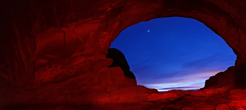 "ARCHES AT SUNRISE - 18 January 2015<br /> <br /> North Window in Red Light - Arches National Park, File #1514817<br /> <br /> Link to Full-Sized Image:  <a href=""http://www.tom-hill.biz/Galleries/Scenics/Utah/i-fcWk3MJ/A"">http://www.tom-hill.biz/Galleries/Scenics/Utah/i-fcWk3MJ/A</a><br /> __________<br /> <br /> (Editor's Update - for some reason the text for this image did not save so it went public without any context for the image.  The text has been updated - 19 Jan 15)<br /> <br /> I'm here in Arches National Park in Utah.  I haven't been here in several years and certainly haven't had this much opportunity for photography like I will on this trip.  After much struggling on where to shoot--I'm still figuring that out--I decided on the Window's and Turret Arch as the subjects for my first morning.  I've shot these subjects many times in the past.  The challenge this time was doing something new and different.<br /> <br /> My main goal for new and different was to include stars.  I've been using stars as a major element in my photography recently.  Usually that involves very early mornings or long nights.  On this occasion it meant getting up at four thirty to be in place by five thirty, a full two hours prior to sunrise.<br /> <br /> I've found you can get reasonable star images if you're at least an hour separated from either sunrise or sunset.  Closer then that, there's too much light and density of the starts diminishes.  In this case, I got there in plenty of time for lots of stars but didn't have one very important element, no clouds.<br /> <br /> When I got there another photographer was already shooting.  I asked, ""how's it going.""  ""Excellent until the clouds rolled in.""  Seems I missed crystal clear black skies by 15 minutes.  Instead, I had this high thin clouds that seriously impacts the luminosity of stars.  The good thing with these types of clouds is it usually means really awesome cloud color near sunrise.  What was I going to do for the next two hours waiting for the sunrise if I couldn't shoot stars?  Well, try stuff, that's what there is to do.<br /> <br /> I went up to the North Window and considered how it would look with colorful clouds through the opening.  Then I thought after I shot a couple of test frames, ""how about some light painting.""  Light painting is a process where you bath your subject with light while the shutter is open.  Essentially, you wave your flashlight back and forth like your painting, hence the term ""Light painting.""<br /> <br /> In this case my flash light wasn't set up with a white light.  Instead I have this new fangled light that's red filtered.  The idea with a red filter is your night vision isn't degraded by red light like a normal white light like can.  As you can with digital photography, I simply gave it a shot, which is what you see here.<br /> <br /> This whole scene was of one particular time.  Unlike other pictures I've posted recent where I collected image data at various times with the approaching sunrise, eventually merging it all together into one image, this photo's image data was collected at one time.  I simply illuminated the arch using my flashlight.   Just to be clear, I did stitch two files together to make the pano you see.  And, I adjusted the final image's tone and contrast like I do for all my images.  Otherwise, no other adjustments.<br /> <br /> Normally I don't do such manipulation.  However, if it works I don't mind.  I just like making sure my viewers know when I'm doing such things. <br /> <br /> As for my opinion on manipulating digital files, I don't mind at all unless the file is somehow advertised as being unmanipulated.  I figure minor tonal edits and such don't need such clarification.  That goes with the territory of digital photography.  But, adding, subtracting, or creating something that clearly didn't exist real-time, I prefer that stuff to be noted.  It's just the way I roll.<br /> <br /> Cheers<br /> <br /> Tom"