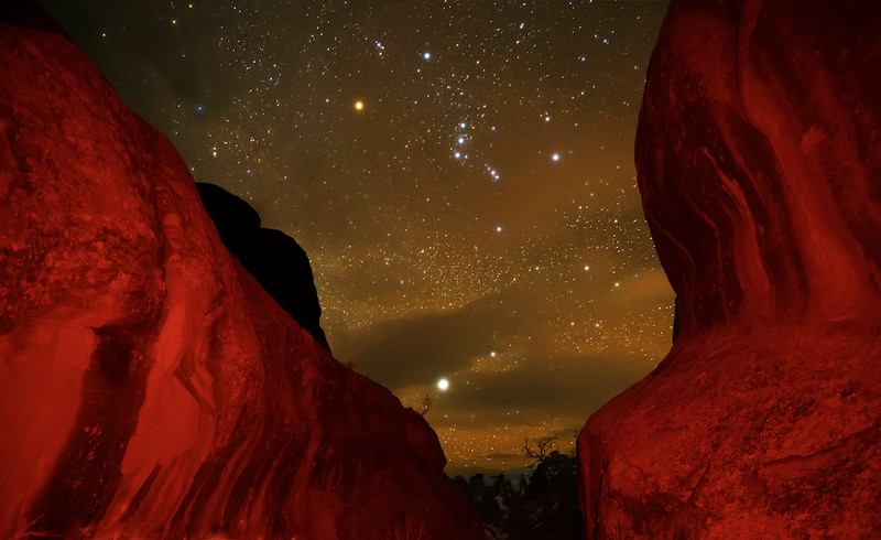 "GRAB NIGHT SHOT - 21 January 2015<br /> <br /> Orion and Fins in Red Light - Arches National Park, File# 1514968<br /> <br /> Link to Full Sized Image - <a href=""http://www.tom-hill.biz/Galleries/Scenics/Utah/i-sZvcc8t/A"">http://www.tom-hill.biz/Galleries/Scenics/Utah/i-sZvcc8t/A</a><br /> __________<br /> <br /> After shooting at night in the middle of a national park, it's a bit of a challenge to walk back to your care through relatively unfamiliar territory.  So much so, it's pretty common when following your headlamp to get off the trail and back track a couple of times.  As a result, it's inevitable to be focus'd just right in front of you, as far as your light beam can go verses looking around and imagining shooting opportunities.<br /> <br /> This time it was a bit different.  I just happened to be looking up while I worked through this narrow opening between two fins when I saw the Orion constellation nicely framed.  Even though I was hell bent on making it back to the car, I thought it was an opportunity to grab a quick shot or two to see what I could make.<br /> <br /> I made one image without the flashlight being used--you know, the red flashlight.  That didn't look so great.  The featureless black blocks on each side of the trail didn't look all that great even though it did a great job framing Orion.  So, I broke out my flashlight, the one I used a couple days ago to light up the North Window  (see here:  <a href=""http://www.tom-hill.biz/Blog/2015/Arches-at-Sunrise-18-January/"">http://www.tom-hill.biz/Blog/2015/Arches-at-Sunrise-18-January/</a>).<br /> <br /> The whole shooting process for this picture took about three minutes.  That included setting up the tripod which involved splaying out all three legs and 2/3rd's of the leg extensions.  In other words, I work fast.<br /> <br /> The only thing I had to do post process was to control the tone a little and apply some noise reduction because I used a very high ISO--i.e. ISO 6400--to really make the stars stand out.<br /> <br /> Cheers<br /> <br /> Tom"