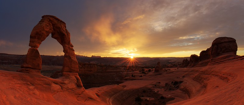 "LAST SUNSET AT ARCHES NATIONAL PARK - 22 January 2015<br /> <br /> Delicate Arch in Winter Sunset - Arches National Park, File# 1515170<br /> <br /> Link to full sized image:  <a href=""http://www.tom-hill.biz/Galleries/Scenics/Utah/i-Jm5CJPh/A"">http://www.tom-hill.biz/Galleries/Scenics/Utah/i-Jm5CJPh/A</a><br /> __________<br /> <br /> This image was taken on my last evening on this trip to Moab, Utah.  This arch is called Delicate Arch.  It might possibly the most photographed arch in the whole world.  Dozens and dozens of people make the relatively difficult trek up the trail.  While the trail isn't especially technically difficult it does have some sustained steep sections with little view of how far it is to go to the destination.  After passing a fairly narrow walkway and around one more bend, there's the arch in all its majestic glory.<br /> <br /> I've made this trek about a dozen times over the years.  The last was three or four years ago when I crested on the ridge just to the opposite side of the arch as you see it here.  Normally, when you get to where I took this image you get the opportunity to enjoy Delicate arch with forty or fifty of the best friends you've never met.  Most people are quite well organized when here and mostly try not to get in the middle of anyone else's picture taking.  That usually means all the photographers are stationed to the right of this image above.  In fact, I have several spectacular images from just that location such as this picture:<br /> <br />  <a href=""http://www.tom-hill.biz/Galleries/Scenics/Utah/i-SnZxCGs/A"">http://www.tom-hill.biz/Galleries/Scenics/Utah/i-SnZxCGs/A</a>)<br /> <br /> As a result, most of the images of Delicate Arch looks very much the same as every other picture of Delicate Arch.  On normal days, it's very difficult to create something innovative.<br /> <br /> This day, the skies were completely overcast.  When I got to the trail parking lot, there seemed more people coming off the mountain than getting ready for the trek up the trail.  I could imagine why because the payback from the effort up the trail wasn't looking very likely.  I even saw one photographer I met that morning up at Mesa Arch.  He seemed to be undecided on whether the trek would be worth the effort as the clouds where quite overcast.  Well, I thought; ""nothing ventured, nothing gained.""  I got my gear together and marched up the hill making it with about 45 minutes prior to sunset.  The sky was still completely overcast with clouds.<br /> <br /> Not about 15 minutes after I made the end of the trail, the other photographer arrived quite exhausted.  And, there wasn't anyone else.  There wee only the two of us, two whole photographers.  We had the whole place to ourselves.  This was a first for me at Delicate Arch.  I've never shot it with only two people, ever.<br /> <br /> I immediately took to shoot compositions I never would've tried with the normal crowd on the site at the risk of being jeered away.  The other photographer and I both planted ourselves almost under Delicate Arch hoping to include a direct view of the setting sun, if the clouds ever broke.<br /> <br /> Sure enough, almost on cue, the clouds parted enough to allow the sun to beam the skies and illuminate the underside of the clouds just as it approached the horizon.  The other photographer and I were changing positions and shooting different compositions as quickly as we could with the fast changing light conditions.<br /> <br /> Just as the sun kissed the horizon a young Japanese fellow made it to the top of the trail so excited.  How did I know?  He was talking out loud to no one how awesome the light show was.  His smile was so wide, he was beaming.  We took his picture with the arch in the foreground and the sun in the background, his arms stretched wide.  His enthusiasm was infectious.<br /> <br /> This visitor pretty much showed off what we all were feeling.  Personally, I felt very lucky and privileged to be up there with perfect light and the place all to myself.  I couldn't have planned it any better if I tried.<br /> <br /> The image here was made from three exposure values to try to capture all the light data so neither the highlights--i.e. the sun--nor the foreground shadows were blown out, meaning they still had detail.  The decision path to process this image using my digital tools was quite complicated.  While I knew exactly what I wanted out of this image--I imagined the final product when I shot the picture up there next to the arch--it still took quite a while to properly create it as you see here.<br /> <br /> Cheers<br /> <br /> Tom"